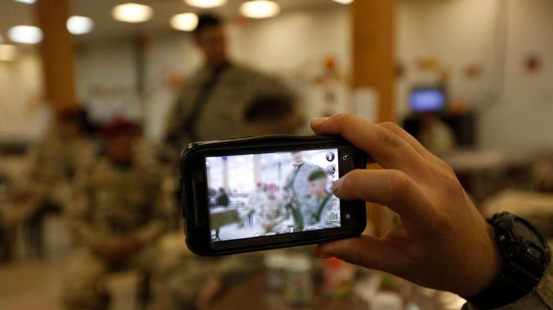 A U.S. Army soldier uses a mobile phone to take a picture of U.S. and Iraqi soldiers at Camp Kalsu