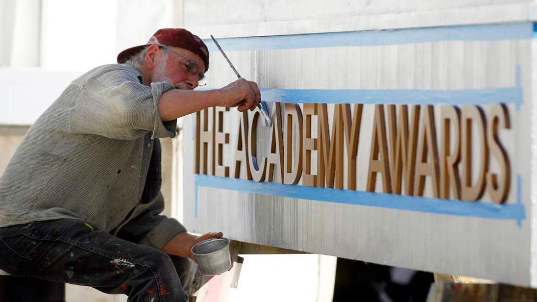 Scenic artist Sam Costa paints a sign in preparation for the 84th Academy Awards in Hollywood, California