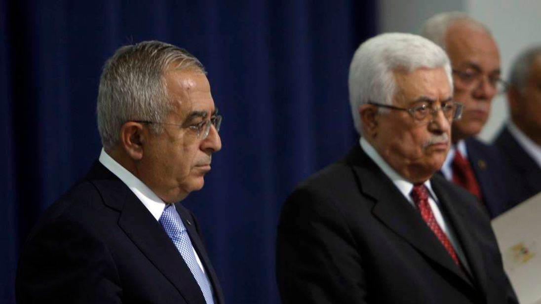 Palestinian Prime Minister Fayyad stands next to President Mahmoud Abbas.