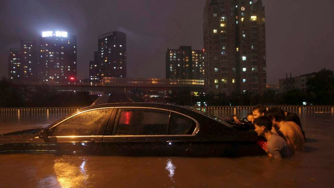 People push a stranded car through flood water