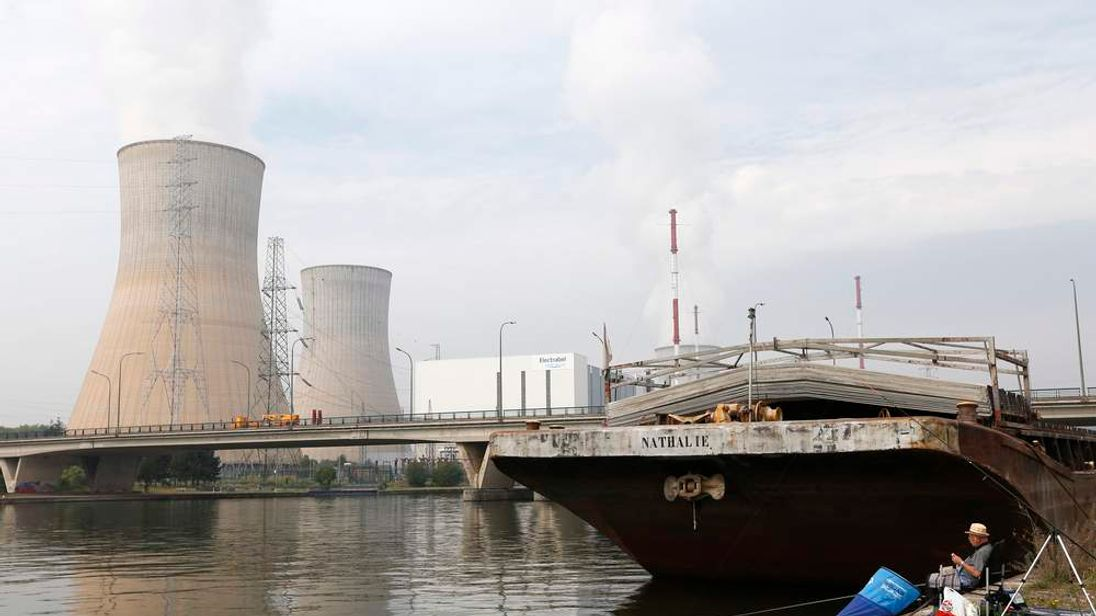 A man fishes in the Hoyoux river as steam billows from the cooling towers of the nuclear plant in Tihange