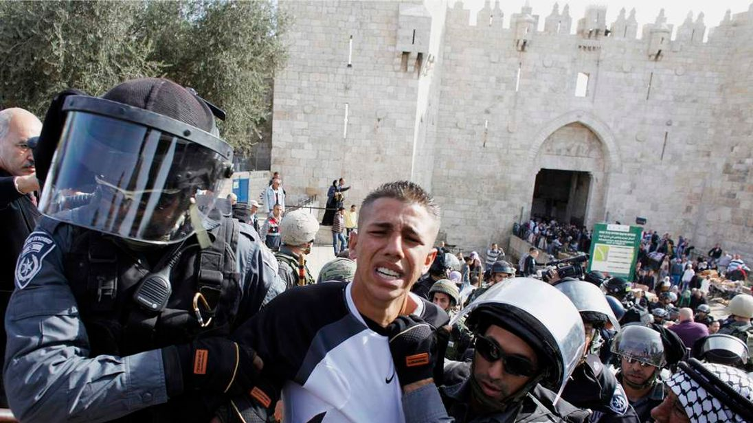 Israeli border police officers detain a Palestinian demonstrator