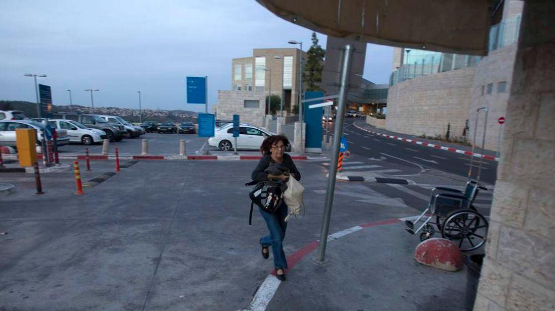 An Israeli woman runs for cover during air raid siren in Jerusalem