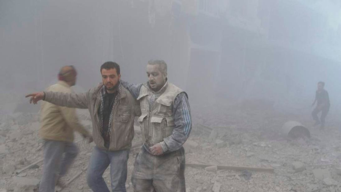 Free Syrian Army fighters are seen near buildings damaged by what activists said were missiles fired by a Syrian Air Force fighter jet loyal to President Bashar al-Assad in the Akraba suburb of Damascus