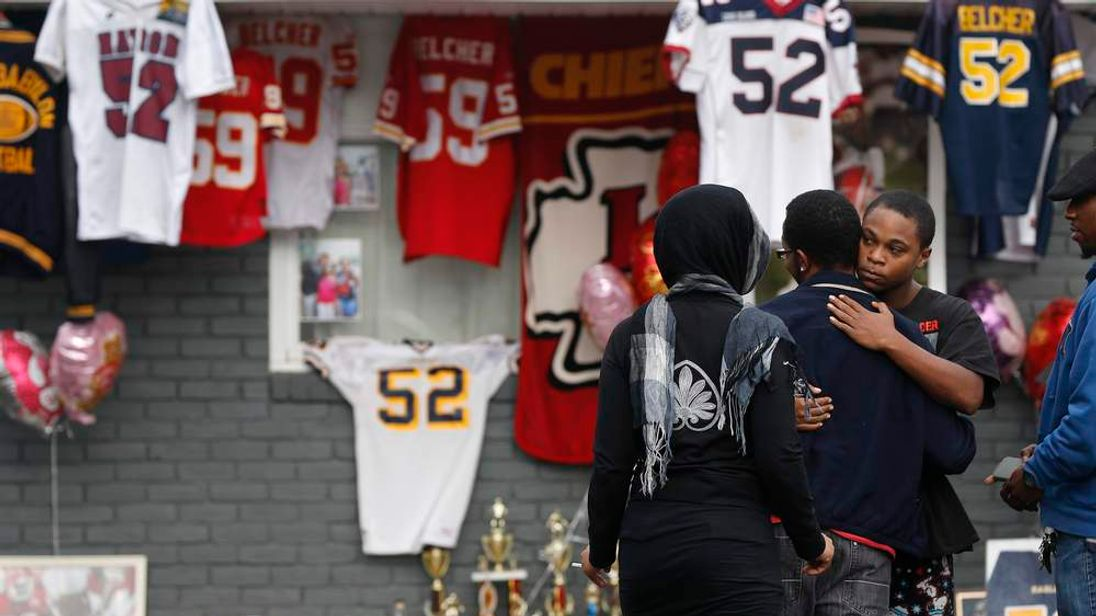 People embrace in front of a makeshift memorial for Kansas City Chiefs football player Jovan Belcher outside his mother's home in West Babylon, New York
