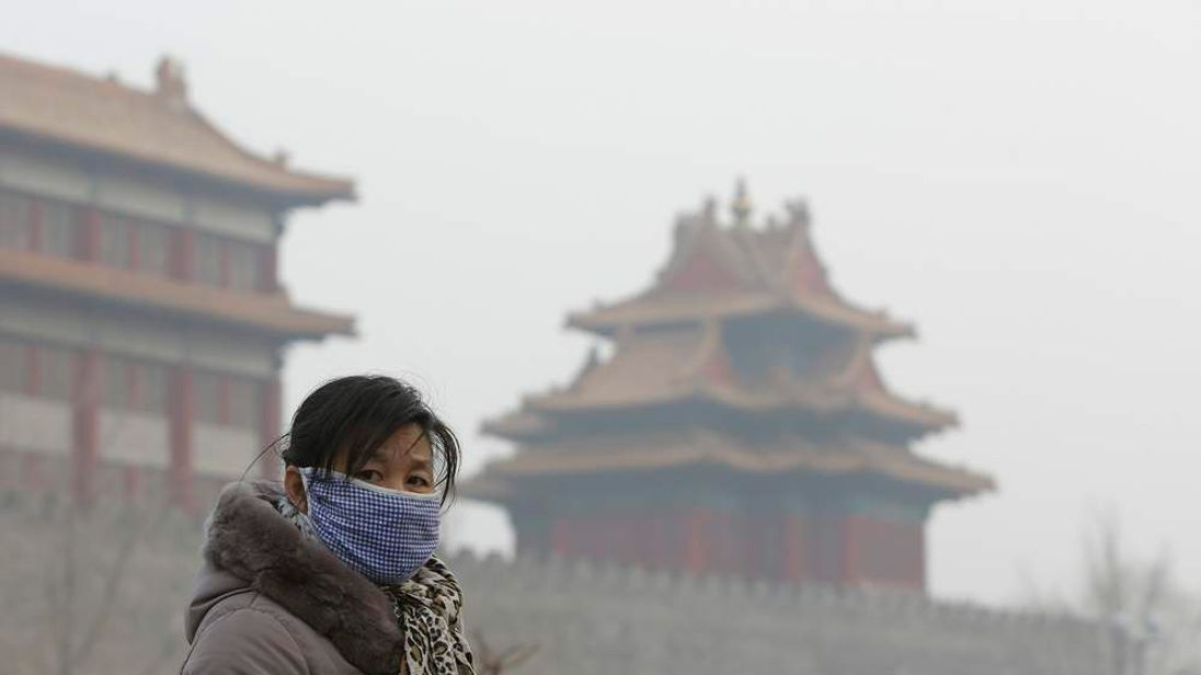 A visitor wearing a mask walks outside the Forbidden City in central Beijing