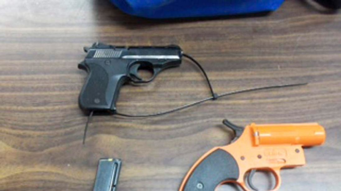 A .22 caliber handgun, its magazine and a flare gun seized by police from a seven-year-old boy at Wave Prep School in New York are pictured in this handout photo