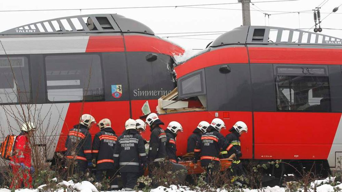 Austrian rescue personnel carries an injured person in front of two demolished S45 trains after a train crash in Vienna