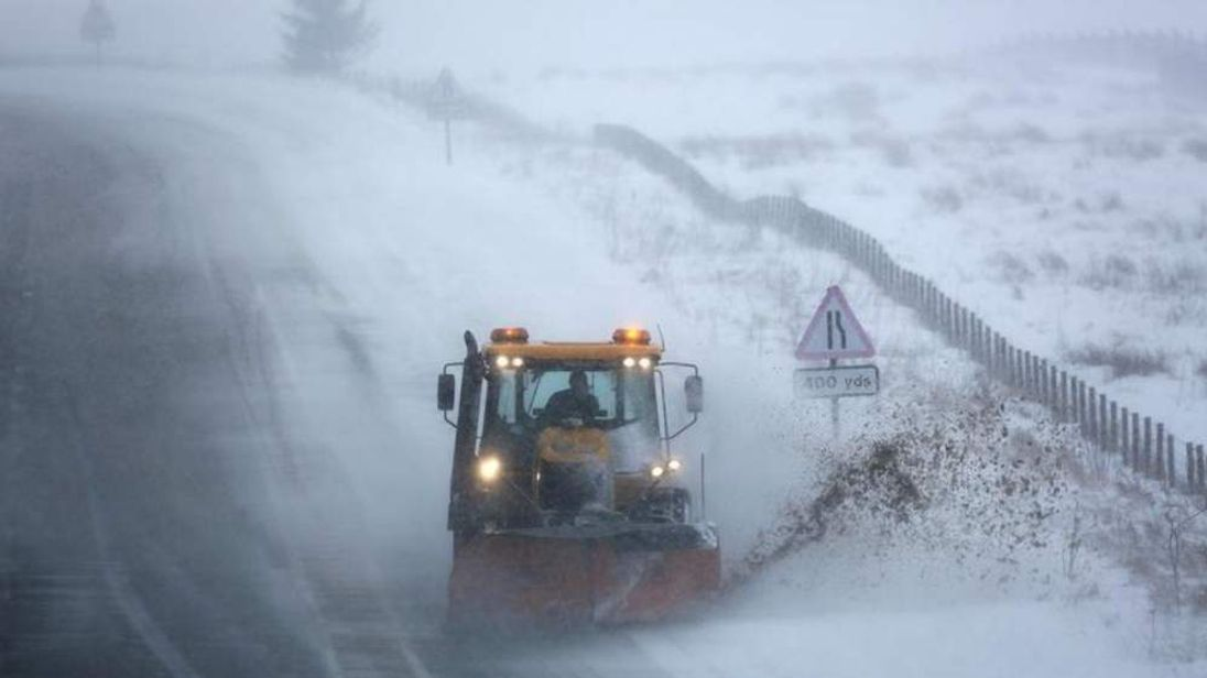 A snow plough drives through drifting snow as it clears the A68 road in southern Scotland