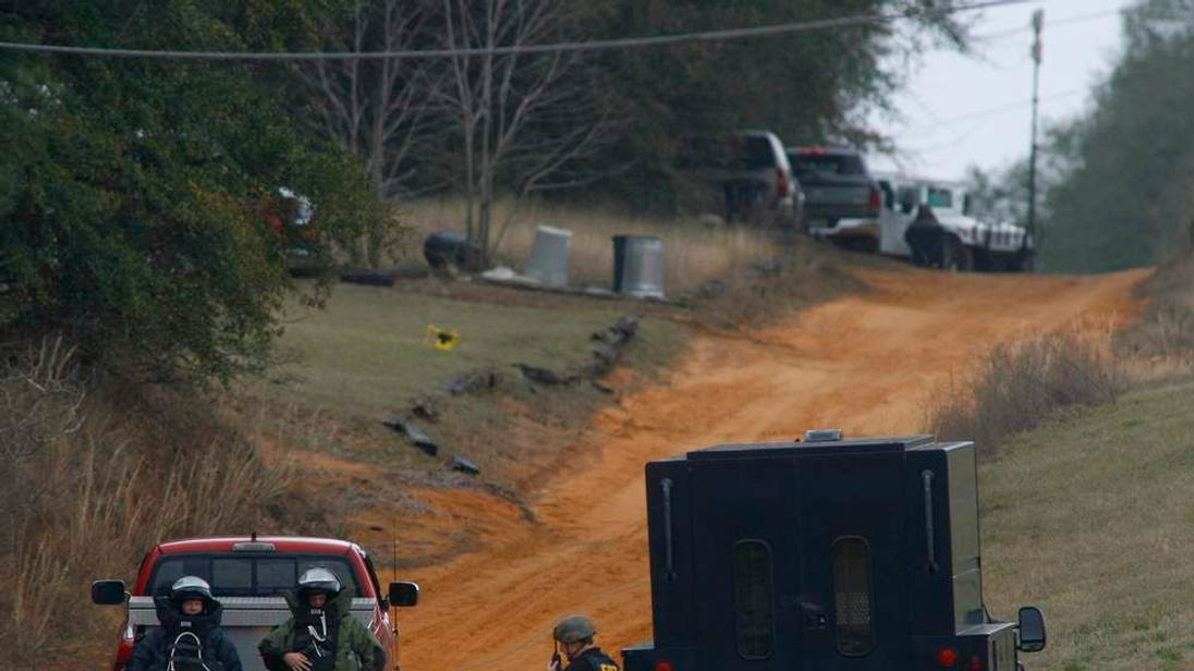 Law enforcement officials in bomb squad protective gear are driven to a scene of a shooting and a bunker as a standoff with a shooter continues in Midland City