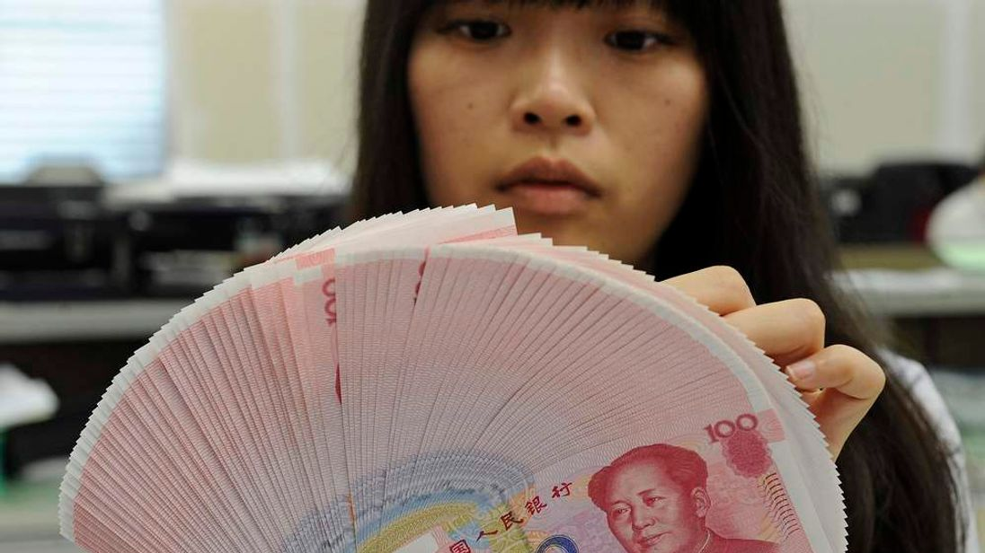 A bank employee counts Chinese yuan notes