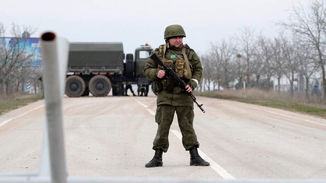 Armed servicemen stand on guard at a roadblock at the Belbek airport near Sevastopol