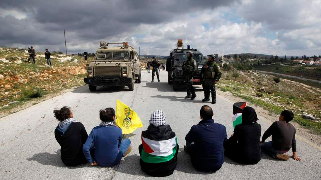 Palestinian activists hold flags as they sit on a road in front of Israeli military vehicles at a weekly protest near Ramallah