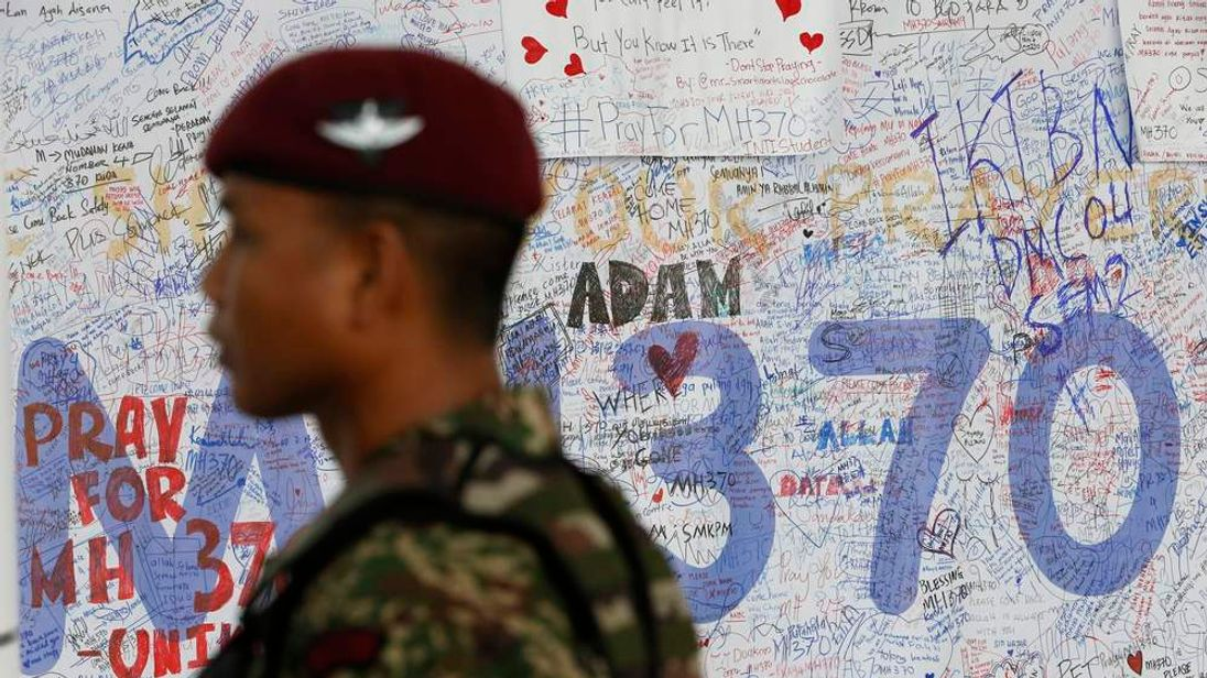 A Malaysian Army paratrooper patrols past banners of well wishes at the viewing gallery of the departure hall at Kuala Lumpur International Airport.