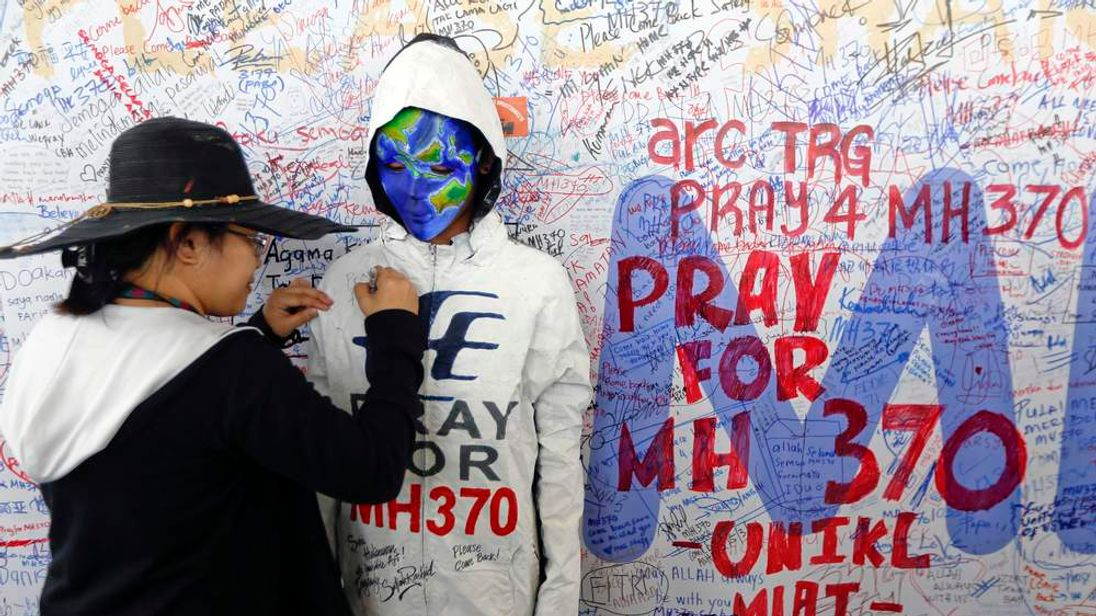 A woman adds her message on the clothes of a model during an art performance in support of the passengers of the missing Malaysia Airlines MH370 at the departure hall of Kuala Lumpur International Airport