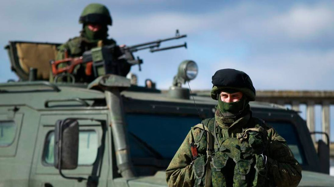 Armed men, believed to be Russians, stand guard near the Ukrainian military base in Perevalnoye