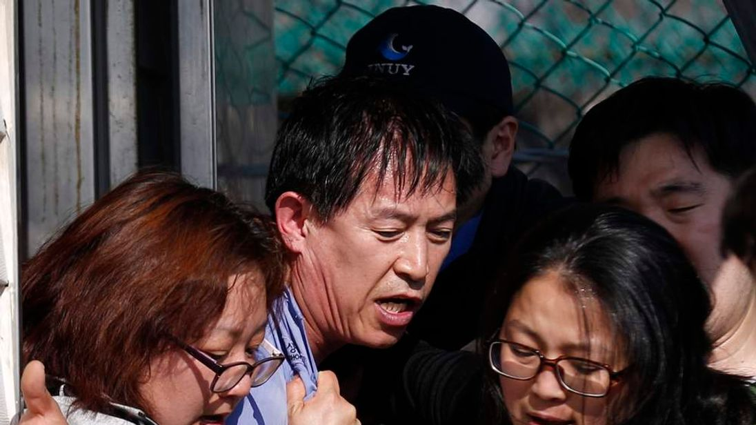Angry family members of passengers on capsized South Korean ferry drag an official out from office to demand for faster and more efficient rescue work in Jindo