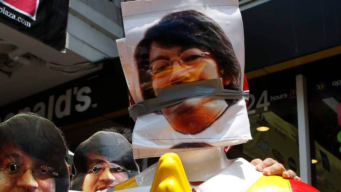 Protesters against military rule wear masks of Sombat Boonngamanong next to a statue of Ronald McDonald during a rally at a shopping district in central Bangkok