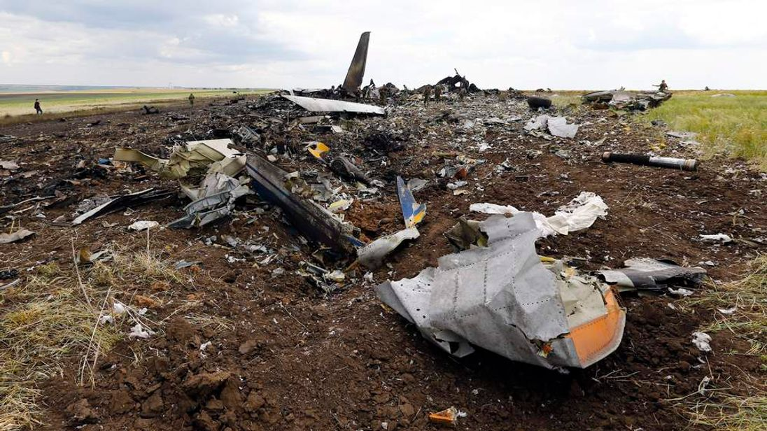 Pro-Russian separatists gather ammunition at the site of the crash of the Il-76 Ukrainian army transport plane in Luhansk