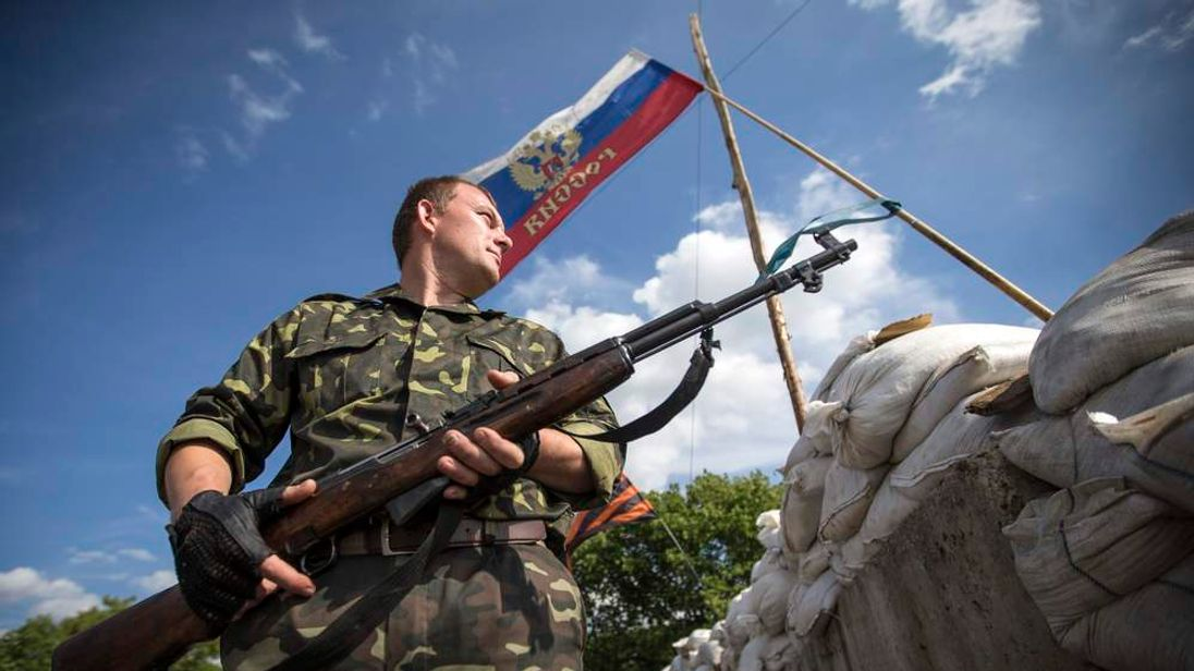 A pro-Russian separatist guards a road checkpoint outside the town of Lysychansk in Luhansk