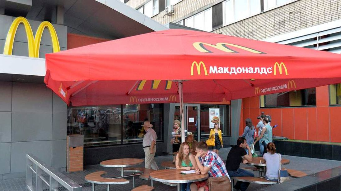 People sit outside closed McDonald's restaurant in Moscow