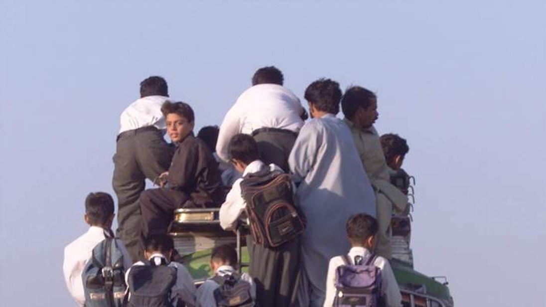 PAKISTANIS RIDE BUS IN ISLAMABAD.
