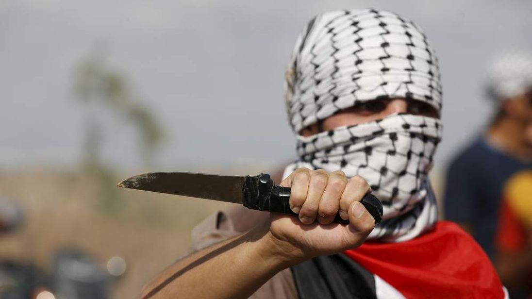 masked Palestinian protester holds a knife during a protest near the Israeli border fence in northeast Gaza