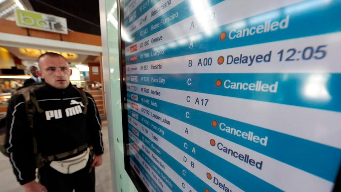 A passenger looks at a flight information board at Nice International airport during a strike by French air traffic controllers