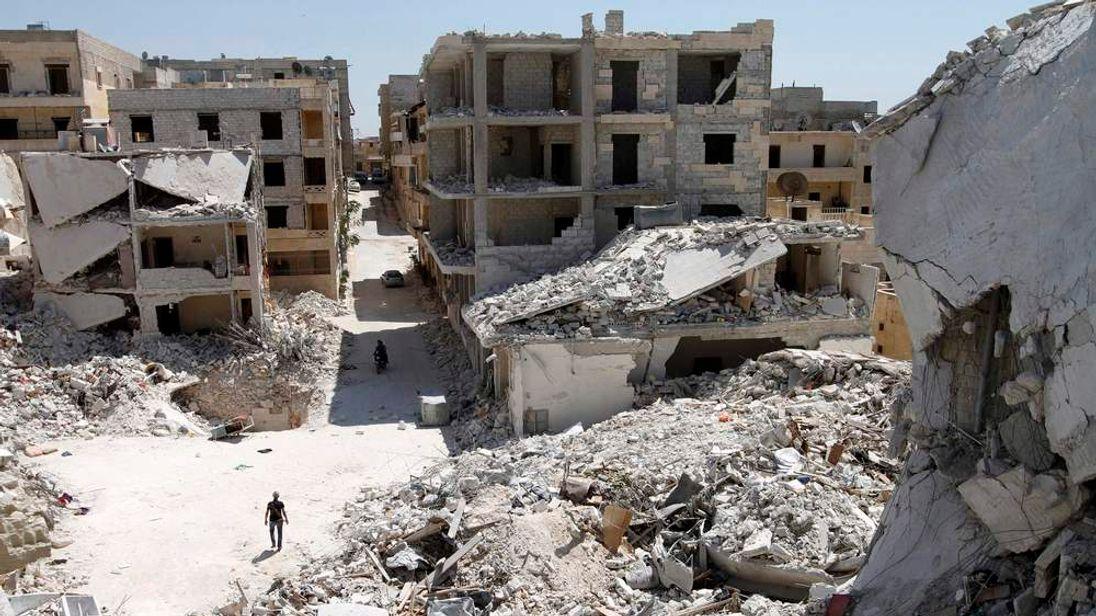 Men ride on a motorbike as a Free Syrian Army fighter walks near damaged buildings in Kefr Hamra, Aleppo