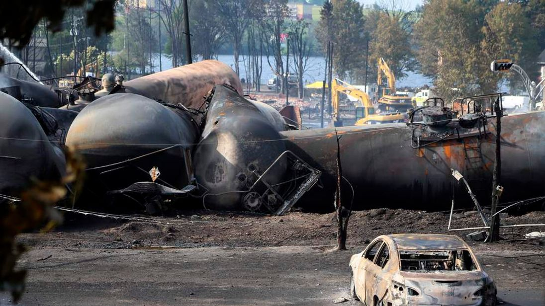 A burnt out vehicle sits near the wreckage of a train car following a train derailment in Lac Megantic Quebec
