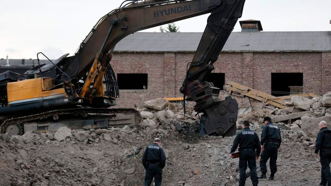 Police officers inspect wreckage of excavator and crater following explosion during earthworks in Euskirchen