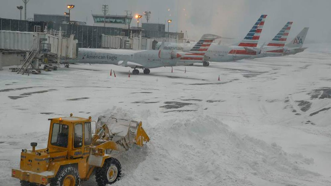 Bulldozer clears the airplane gate areas of snow at LaGuardia Airport in New York