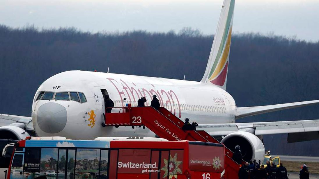 Passengers climb down an airplane ladder with their hands on their heads as police officers stand around hijacked Ethiopian Airlines flight ET 702 at Cointrin airport in Geneva