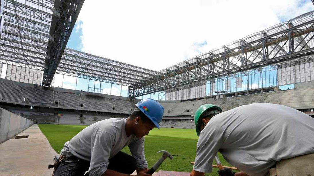 Workers are pictured inside the Arena da Baixada soccer stadium