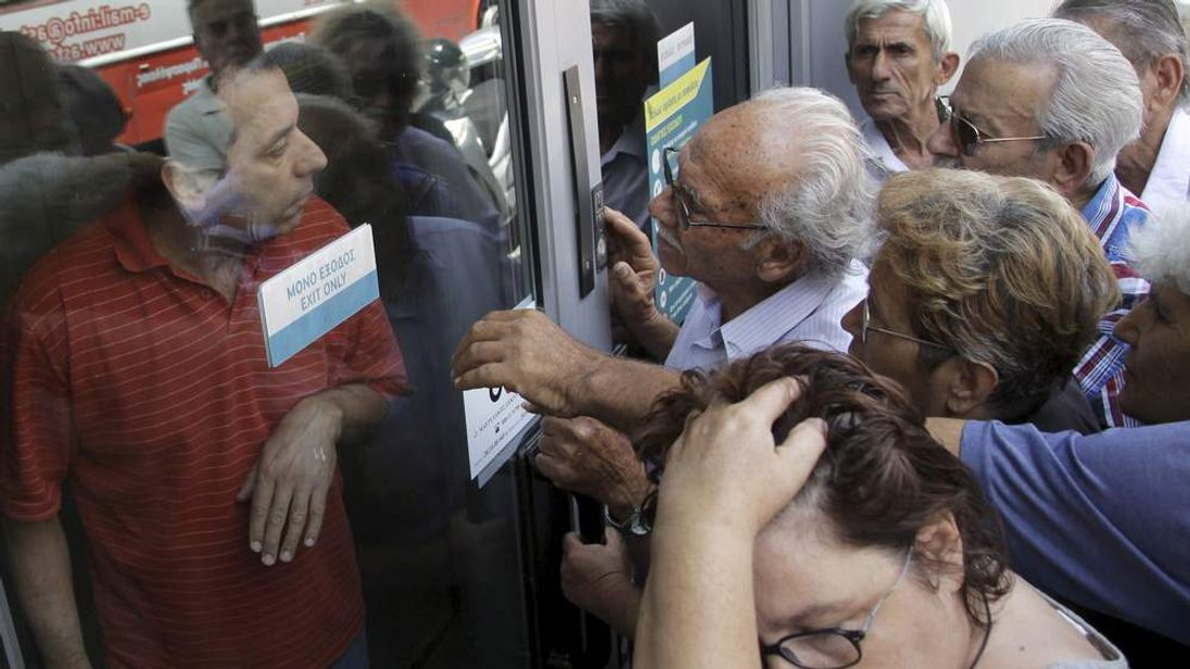 Pensioners waiting outside a closed National Bank branch and hoping to get their pensions, argue with a bank employee in Iraklio on the island of Crete
