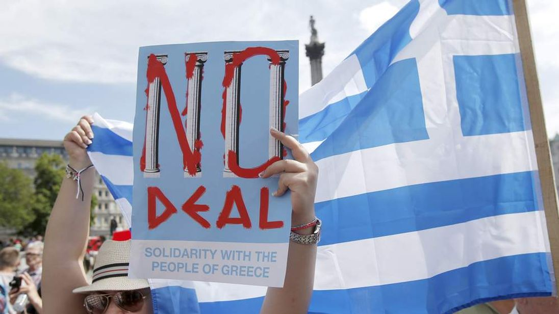A woman holds the flag of Greece and a poster in favour of the 'NO' campaign, at the 'Greek solidarity festival' in Trafalgar Square, London