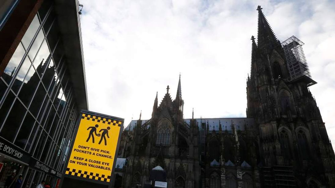 Sign warning against pickpockets is displayed outside main railway station and in front of Cologne Cathedral