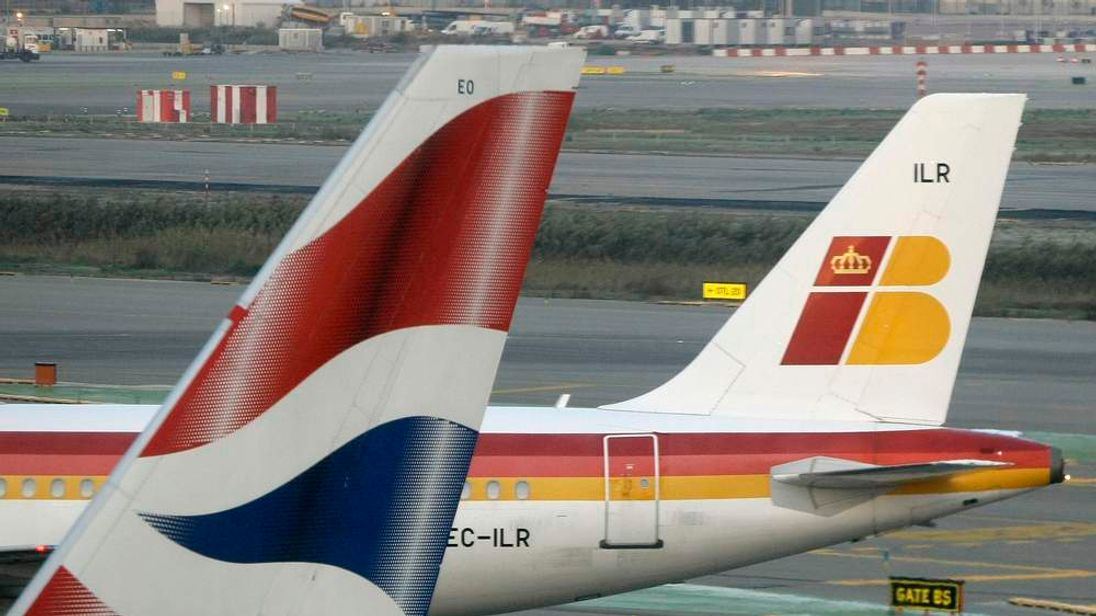 An Iberia jet passes a British Airways jet at Barcelona Airport