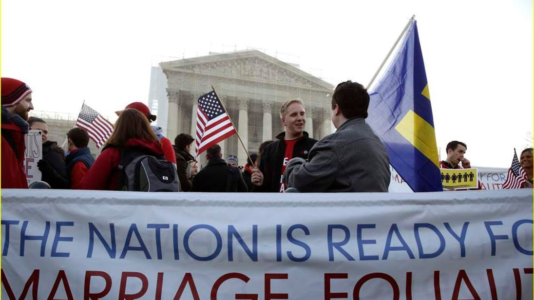 Protesters stand next to a banner outside of the U.S. Supreme Court in Washington