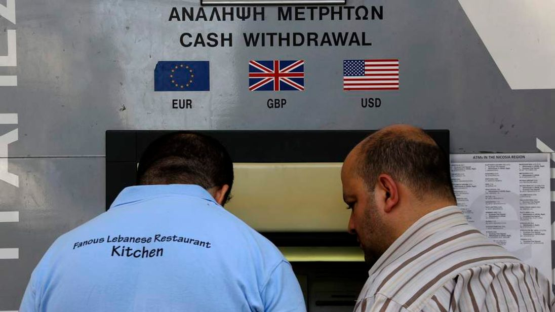 People make transactions at an ATM in Nicosia