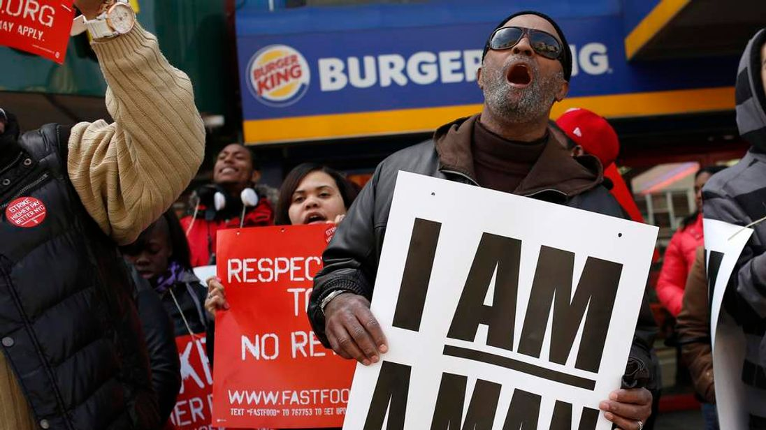 People demonstrate outside a Burger King franchise on 116th street in New York