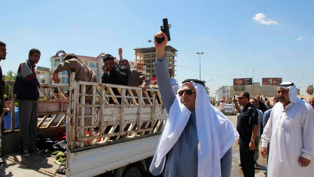 A man fires a gun during a funeral for protesters who died during a clash between Iraqi forces and Sunni Muslim protesters in Kirkuk