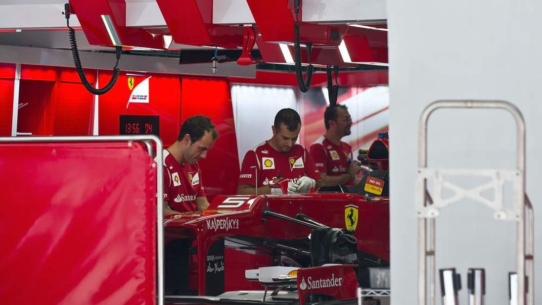 Ferrari mechanics working on Fernando Alonso's car which will carry the Italian navy flag during the Indian Grand Prix