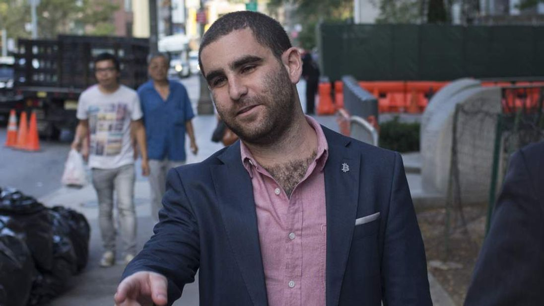 Bitcoin promoter Charlie Shrem points to a obstacle behind a photographer as he walks out of federal court in Lower Manhattan,