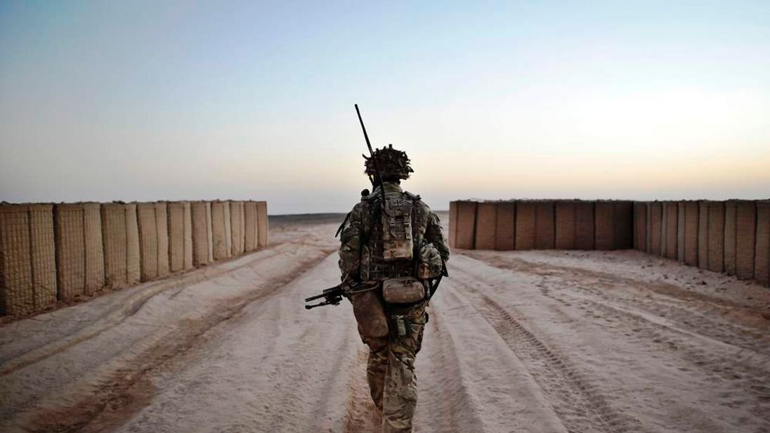 A soldier from the 1st Battalion Royal Regiment Fusiliers leaves the security of the camp walls to conduct a dawn foot patrol in the Nahr-e Saraj district, Helmand Province