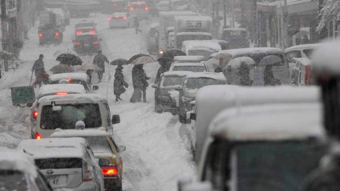 People cross a snow-covered street as traffic comes to a stop during a heavy snowfall in Tokyo