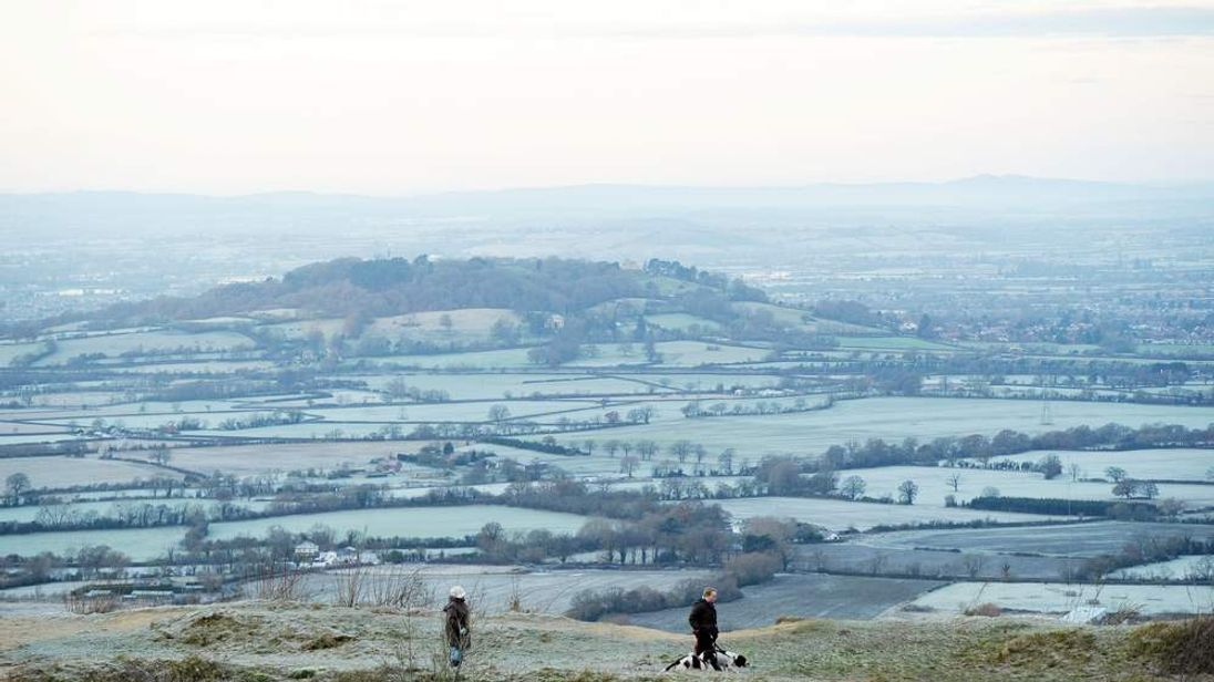 People walk their dogs at Crickley Hill Country Park as they look over frozen farmland