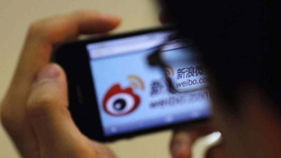 A man holds an iPhone as he visits Sina's Weibo microblogging site