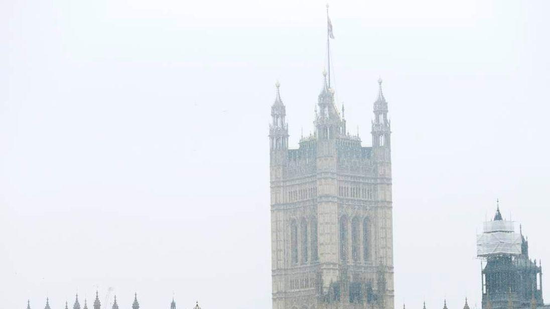 People walk cross Westminster Bridge during snowfall in central London