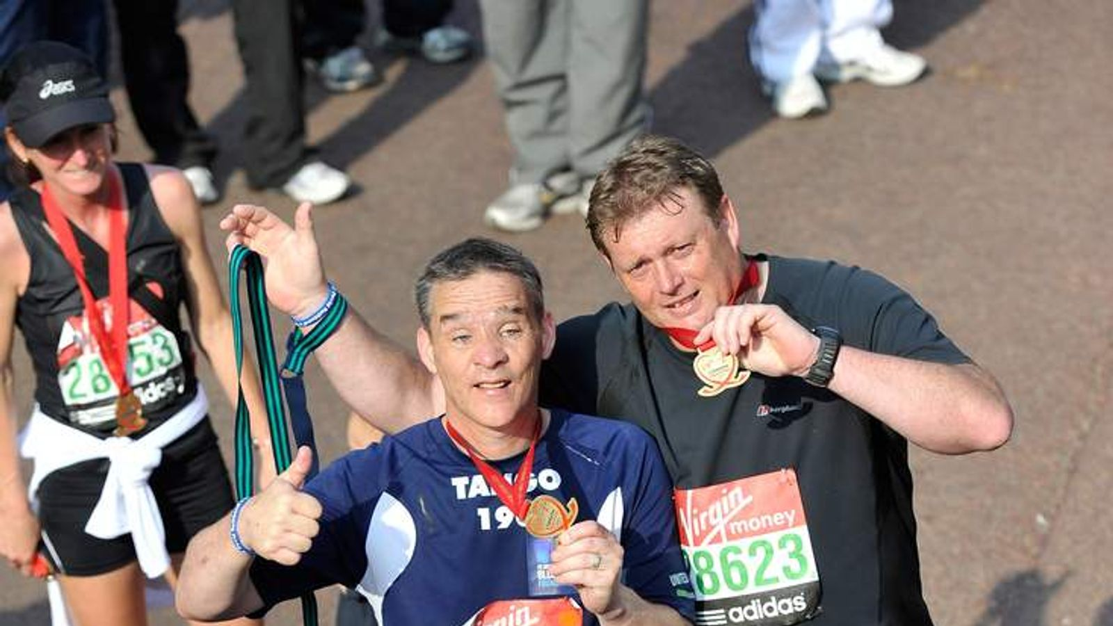 Pc David Rathband (L) completes the 2011 Virgin London Marathon